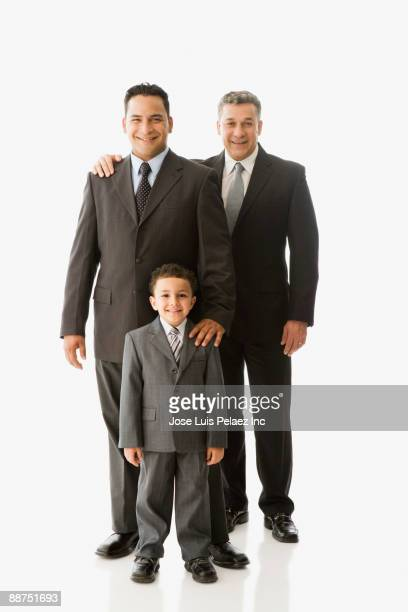 Hispanic businessman with father and son dressed in suits