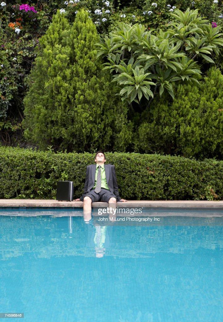 Hispanic businessman with feet in swimming pool : Stock Photo