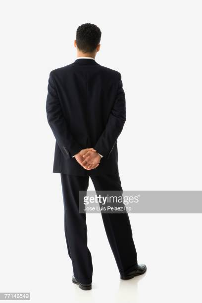 Hispanic businessman with hands behind back