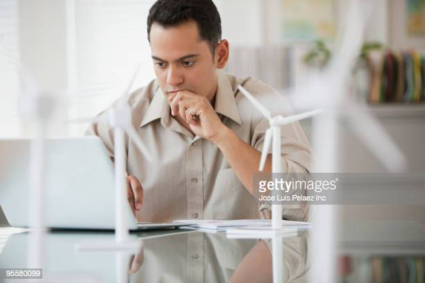 Hispanic businessman with laptop and wind turbine models