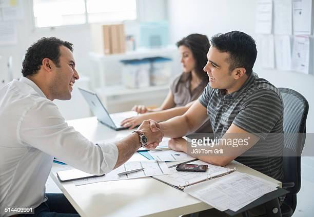 Hispanic businessmen shaking hands in office