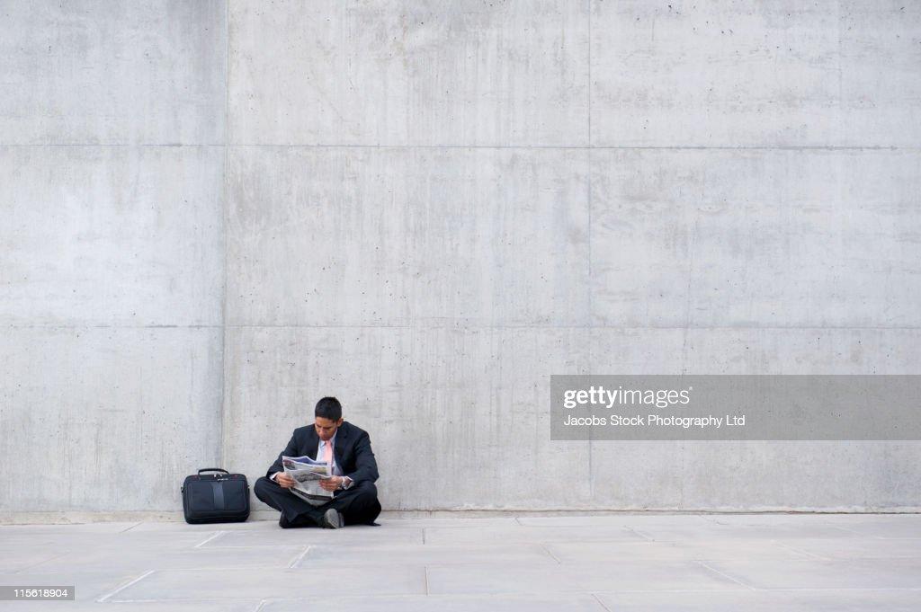 Hispanic businessmen sitting on ground reading newspaper