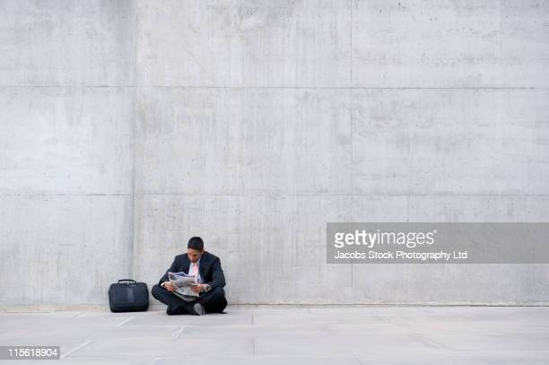 Hispanic businessmen sitting on ground reading newspaper