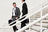 Hispanic businesspeople walking down stairs