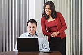 Hispanic businesswoman and businessman looking at computer