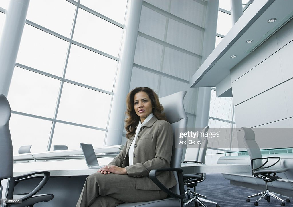 Hispanic businesswoman at conference table