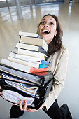 Hispanic businesswoman carrying a stack of books trying to balance