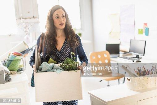 Hispanic businesswoman carrying cardboard box in office