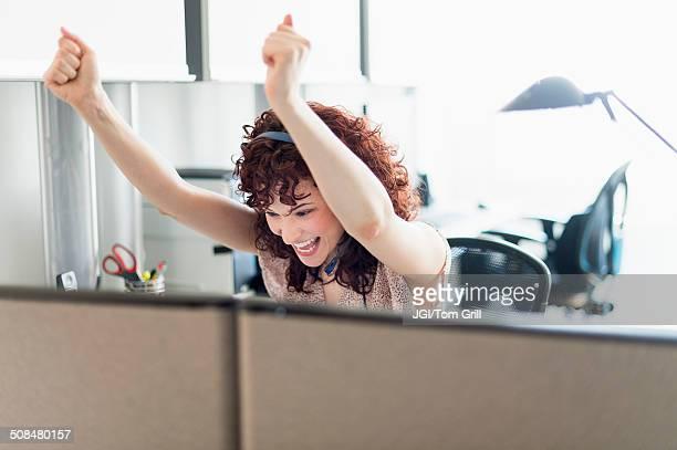 Hispanic businesswoman cheering in office