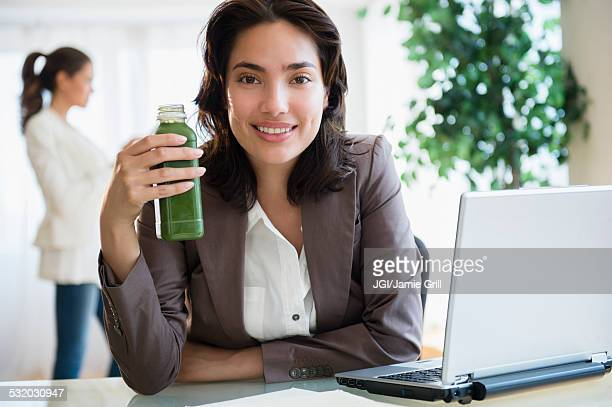Hispanic businesswoman drinking green juice at desk in office