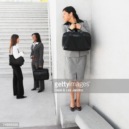 Hispanic businesswoman eavesdropping on coworkers