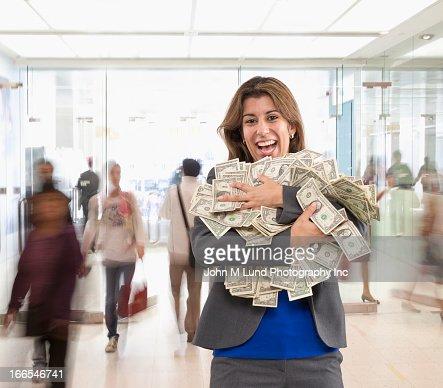 Hispanic businesswoman holding armful of dollar bills : Stock Photo