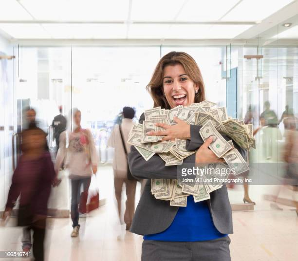 Hispanic businesswoman holding armful of dollar bills