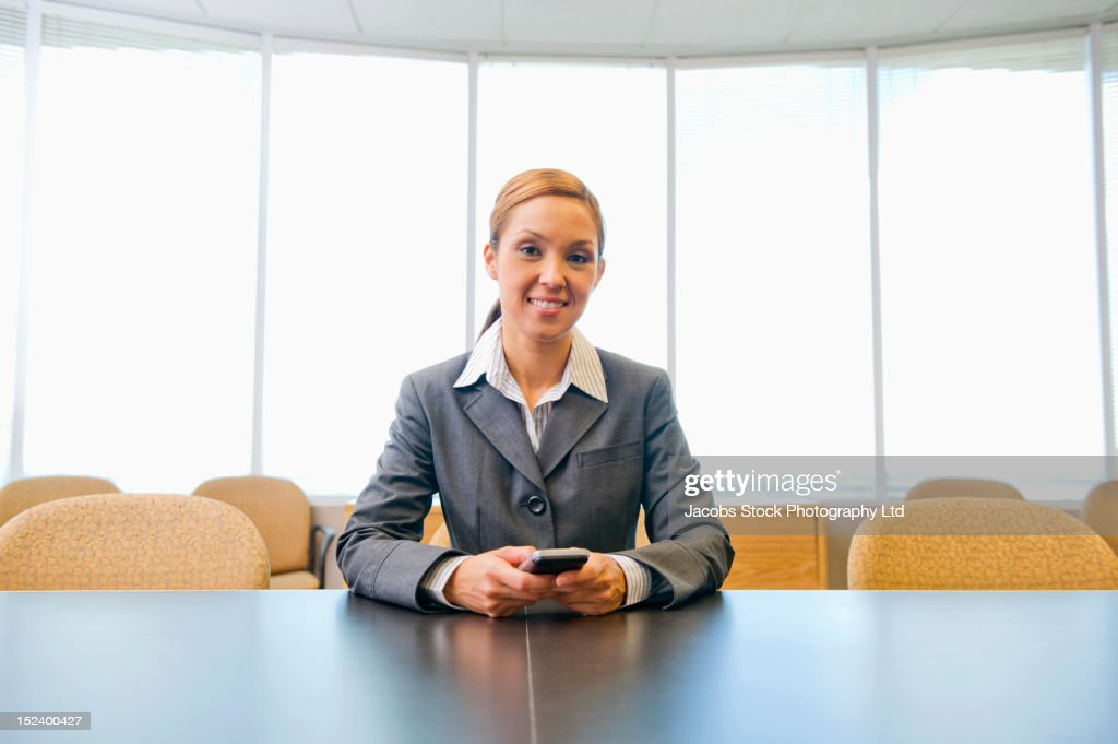 Hispanic businesswoman holding cell phone : Stock Photo