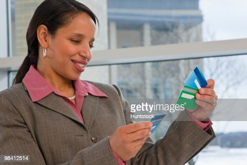 Hispanic businesswoman holding credit cards : Stock-Foto