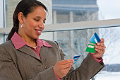Hispanic businesswoman holding credit cards