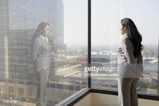 Hispanic businesswoman looking out a window : Foto de stock