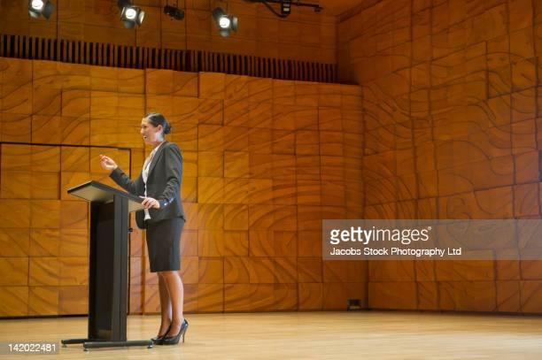 Hispanic businesswoman making speech at podium