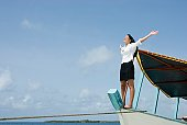 Hispanic businesswoman on boat with arms raised