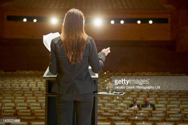 Hispanic businesswoman practicing speech in empty auditorium