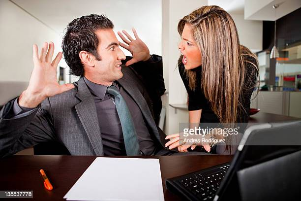 Hispanic businesswoman shouting at co-worker in office