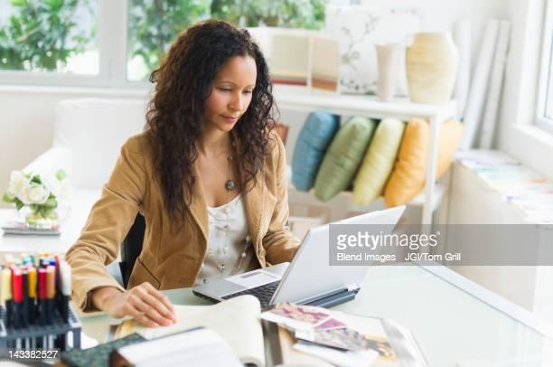 Hispanic businesswoman sitting at desk using laptop