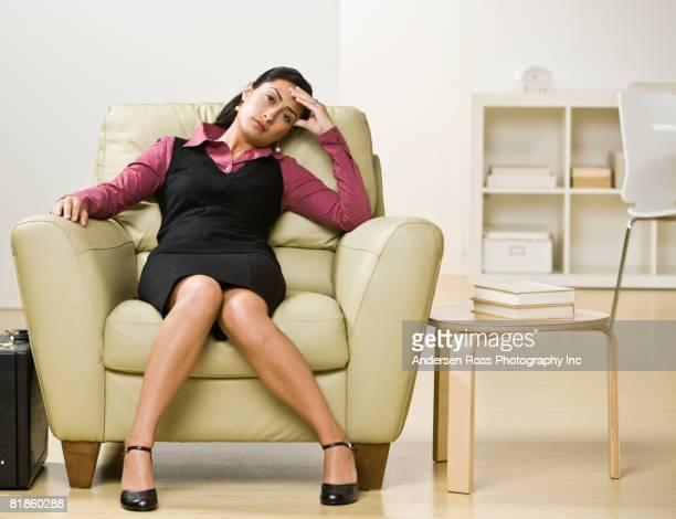 Hispanic businesswoman sitting in armchair