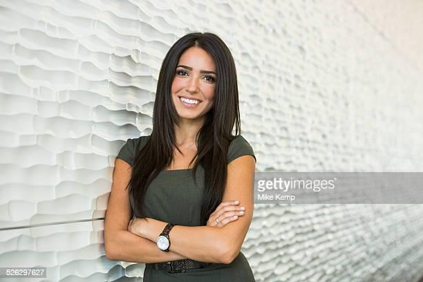 Hispanic businesswoman smiling near wall