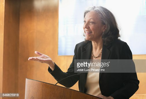 Hispanic businesswoman speaking at podium