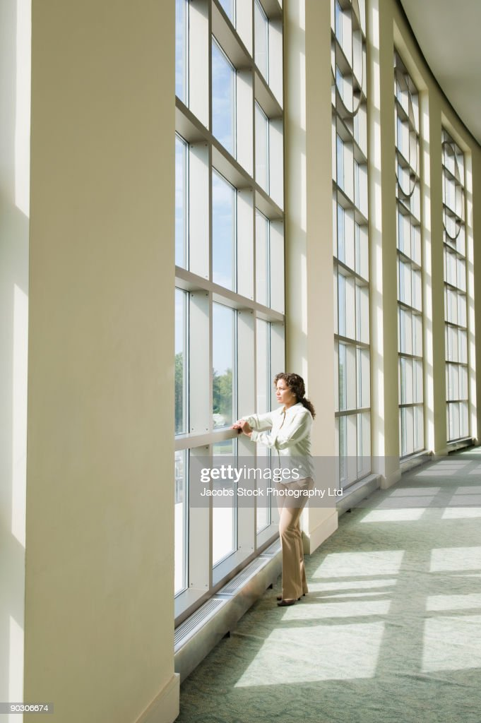 Hispanic businesswoman standing in office lobby : Stock Photo