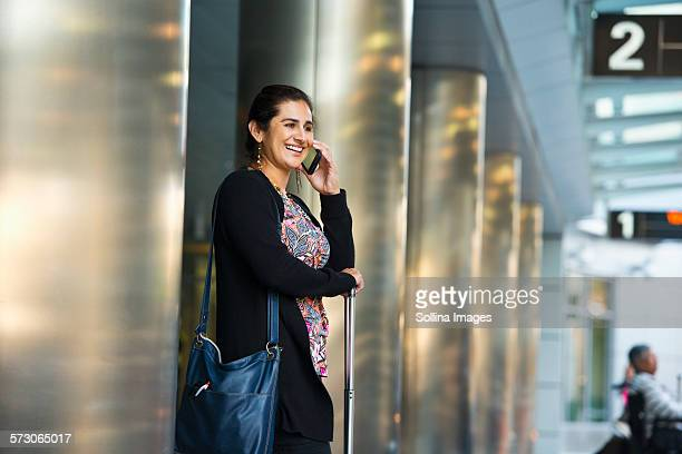 Hispanic businesswoman talking on cell phone in airport