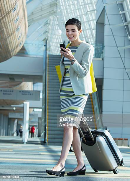 Hispanic businesswoman using cell phone in airport