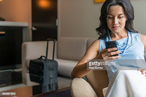 Hispanic businesswoman using cell phone in office lobby