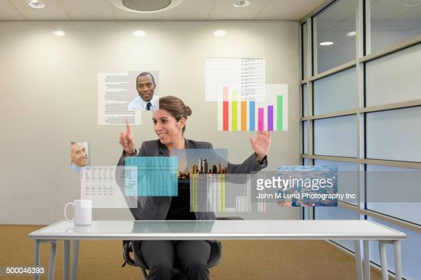Hispanic businesswoman using futuristic screens at desk