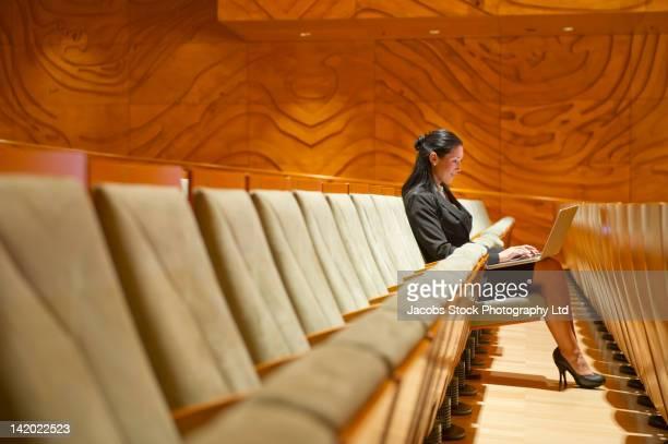 Hispanic businesswoman using laptop in empty auditorium