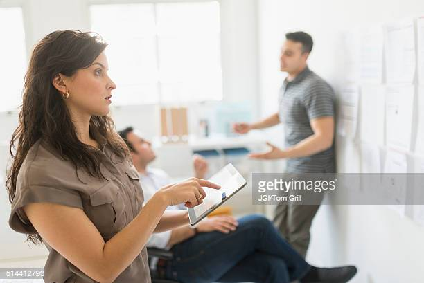 Hispanic businesswoman using tablet computer in office
