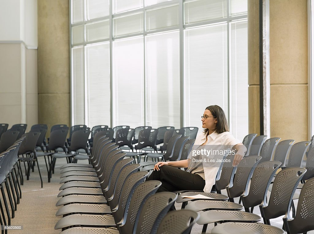 Hispanic businesswoman waiting in empty conference room : Stock Photo