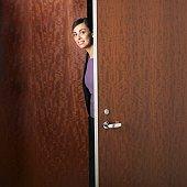 Hispanic businesswoman walking through doorway