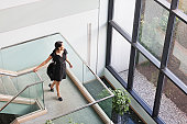 Hispanic businesswoman with briefcase on stairs on office building