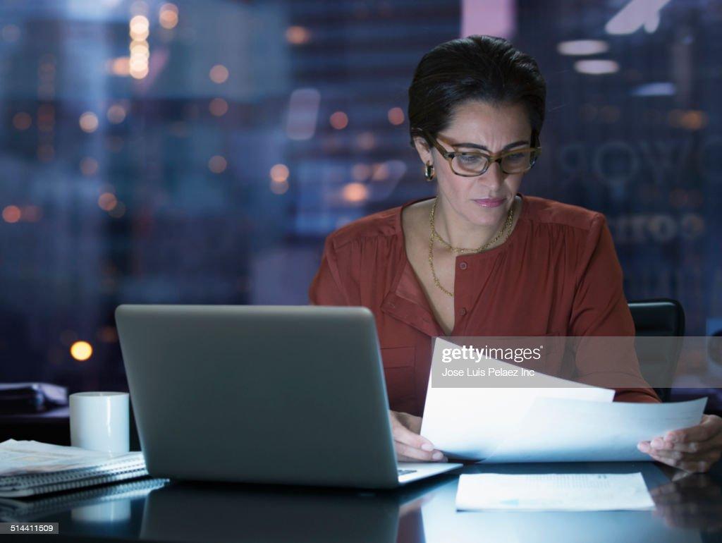 Hispanic businesswoman working at desk at night