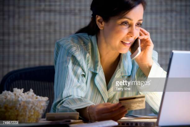 Hispanic businesswoman working in pajamas