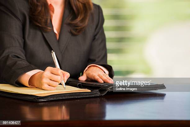 Hispanic businesswoman writing notes at desk