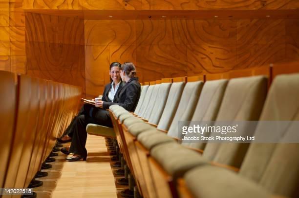 Hispanic businesswomen sitting in empty auditorium