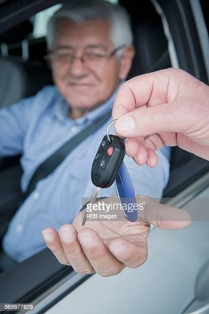 Hispanic car salesman handing keys to customer