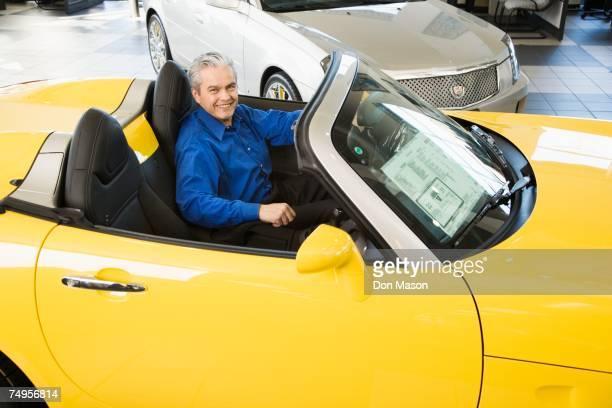 Hispanic car salesman sitting in new car