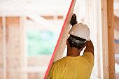 Hispanic carpenter carrying sheathing at a house under construction