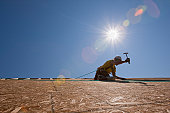 Hispanic carpenter using a hammer on the roofing at a house under construction
