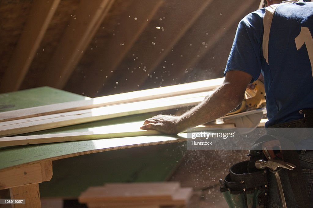 Hispanic carpenter using circular saw on trim strip at a house under construction