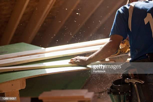 Hispanic carpenter using circular saw on trim strip at a house under construction
