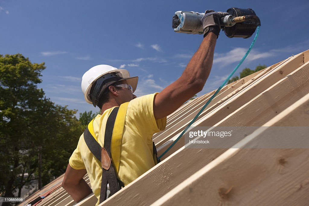 Hispanic carpenter using nail gun on roofing at a house under construction  Stock Photo : roof carpenter - memphite.com